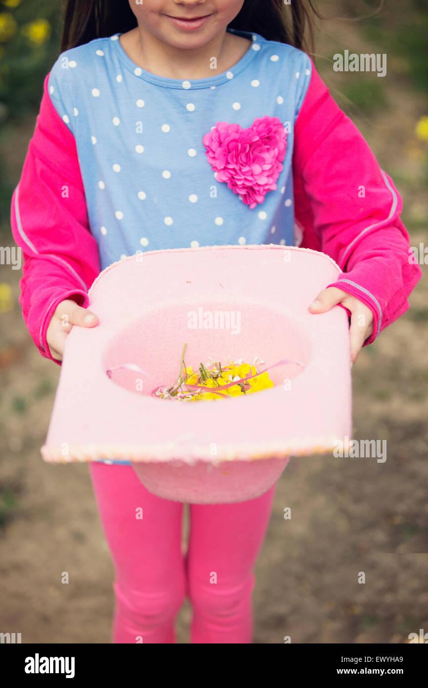 Girl holding un chapeau rempli de fleurs Photo Stock