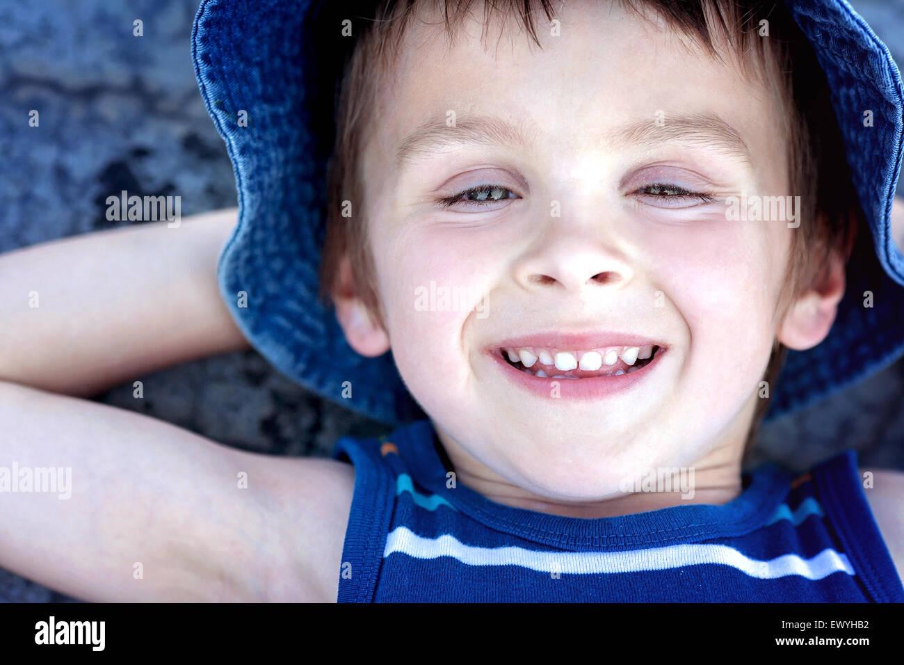 Vue aérienne d'un garçon allongé sur le sol avec ses mains derrière sa tête Photo Stock