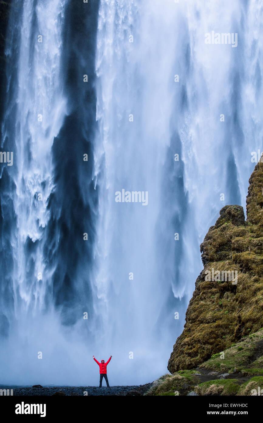 L'homme avec son bras en l'air debout au pied de la cascade de Skogafoss, Islande Photo Stock