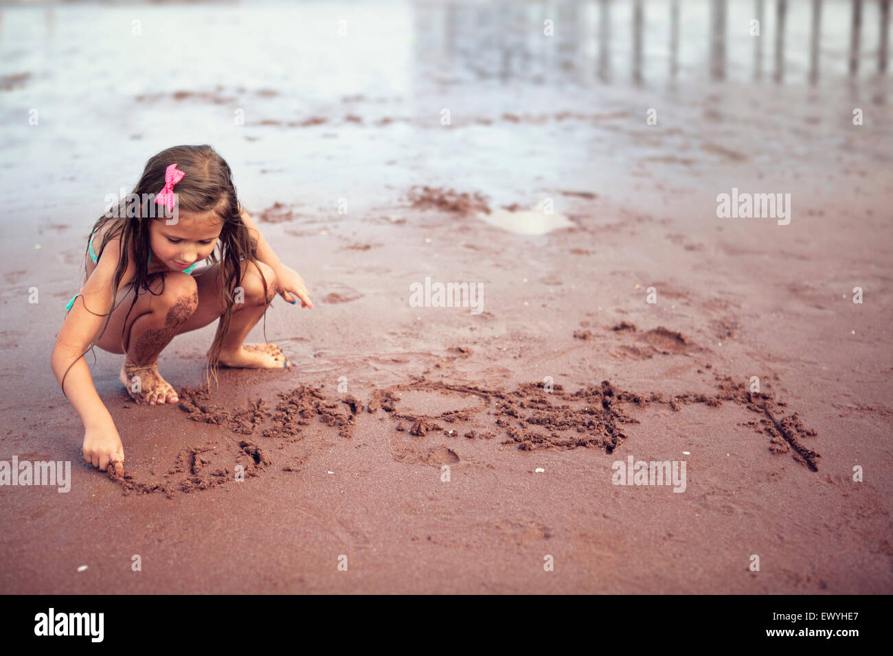 Girl écrit dans le sable Photo Stock