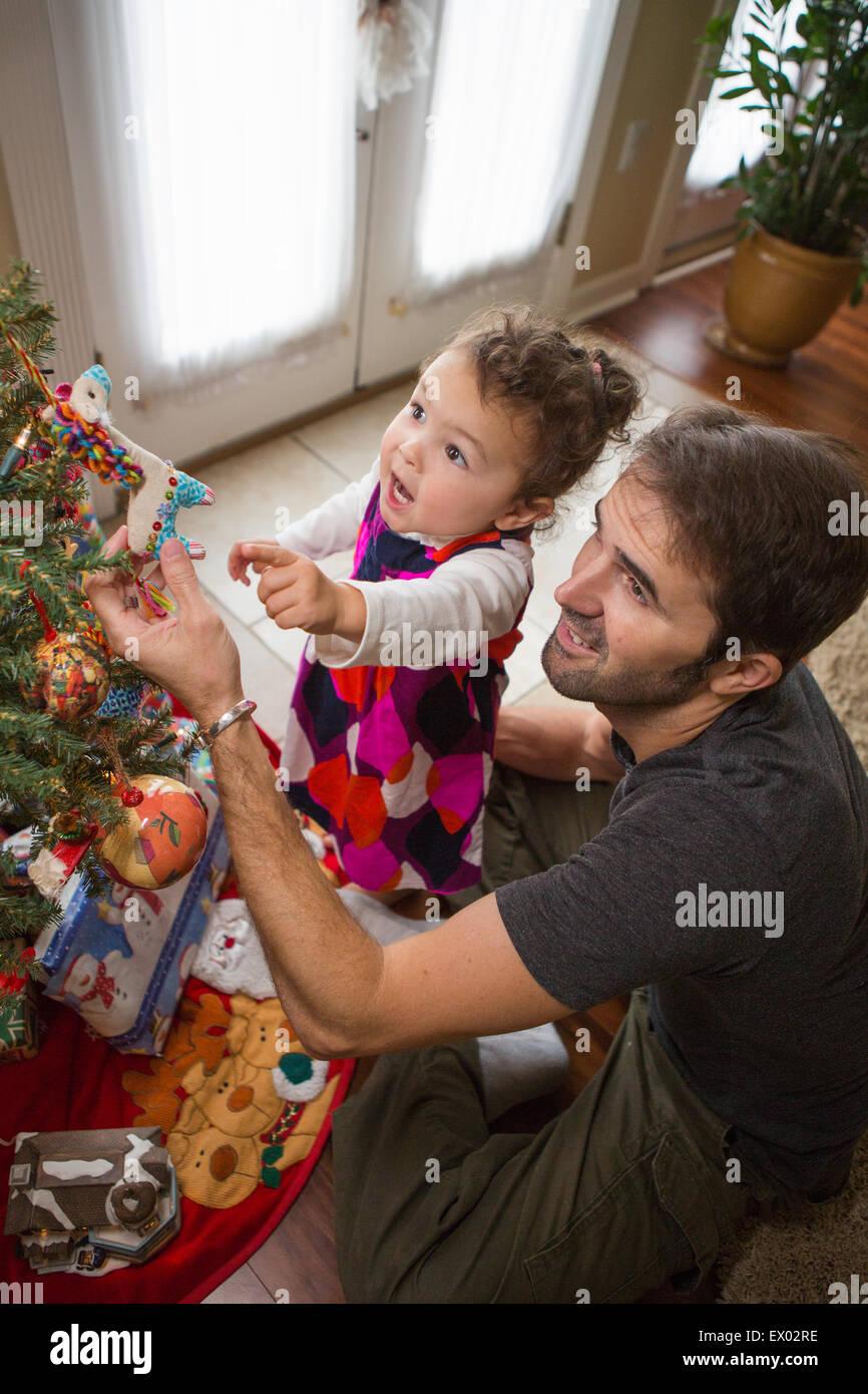 Père et fille de placer les boules de Noël sur un arbre Photo Stock