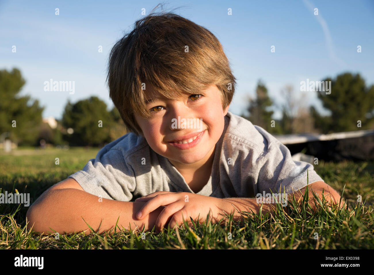Portrait of smiling boy lying on grass park Photo Stock