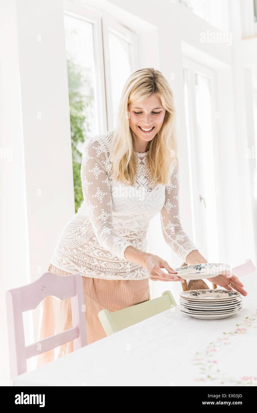 Femme portant des plaques sur table de salle à manger pour partie Photo Stock