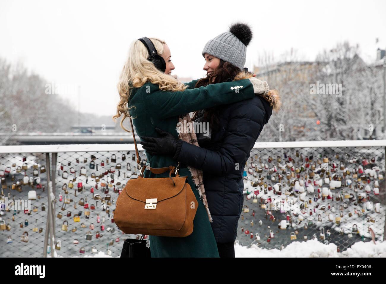 Deux Mid adult women hugging on bridge Photo Stock