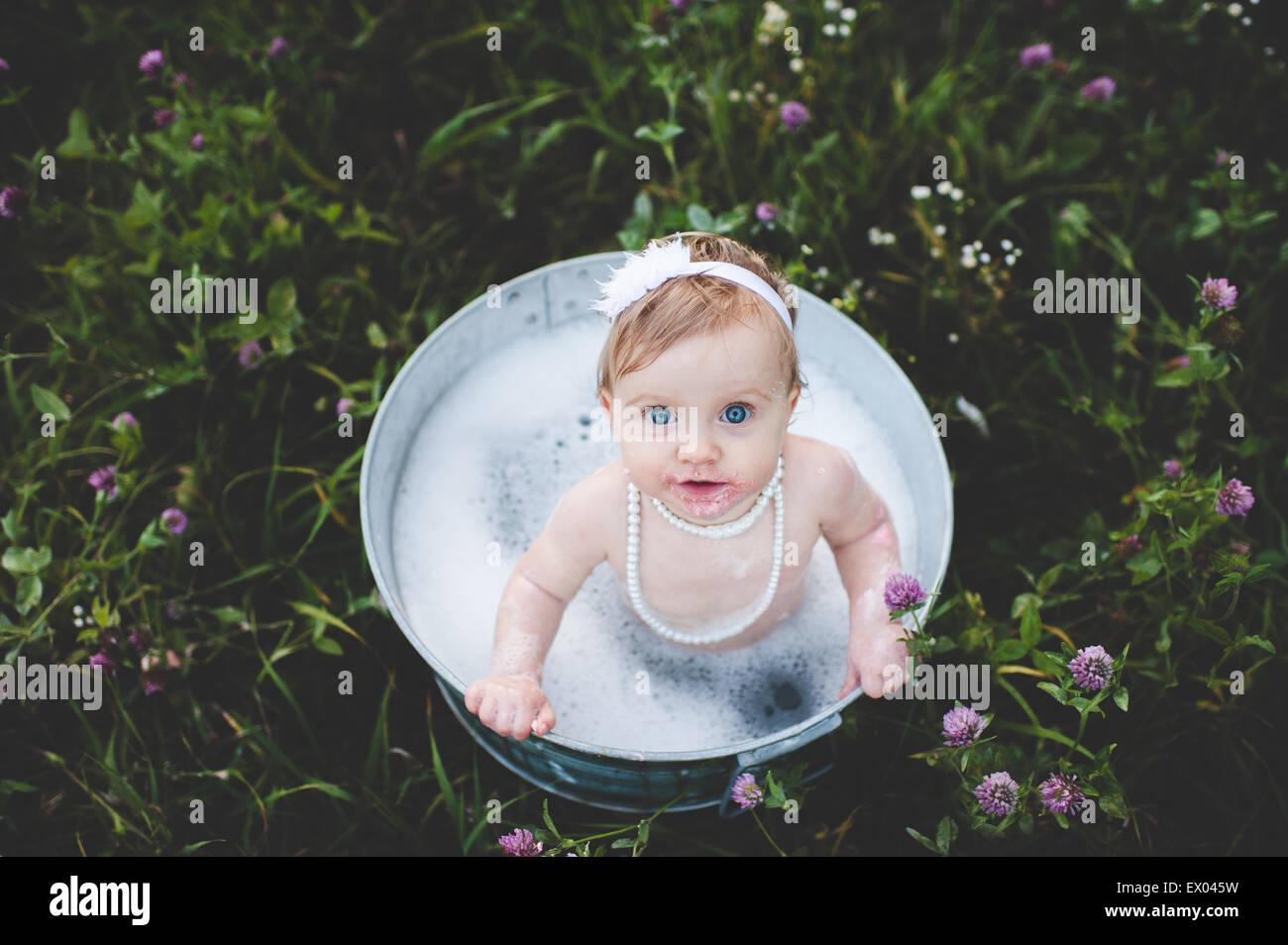 Vue de dessus de petite fille baignant dans un bain d'étain dans une prairie de fleurs sauvages Banque D'Images