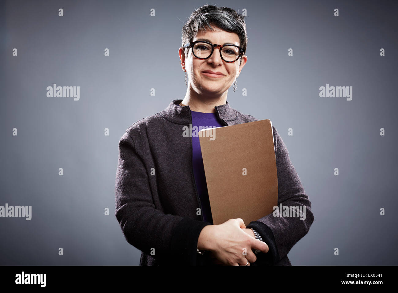 Studio portrait of mature businesswoman with clipboard Photo Stock
