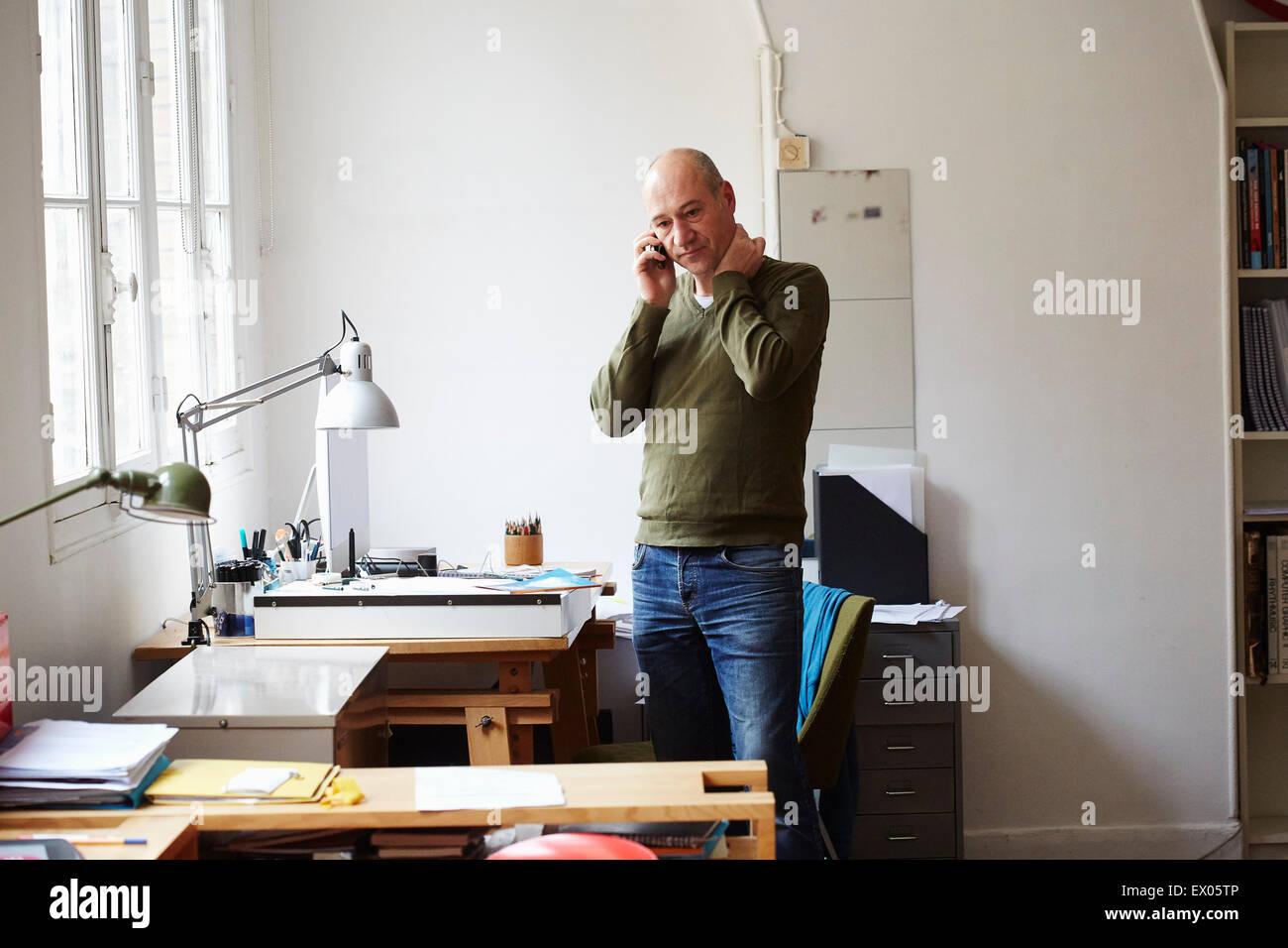 Homme mûr sur le téléphone dans creative studio Photo Stock
