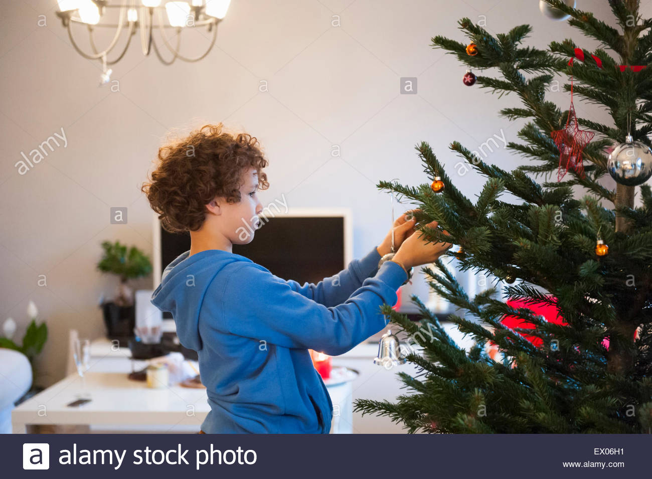 Boy hanging on Christmas Tree decorations Photo Stock