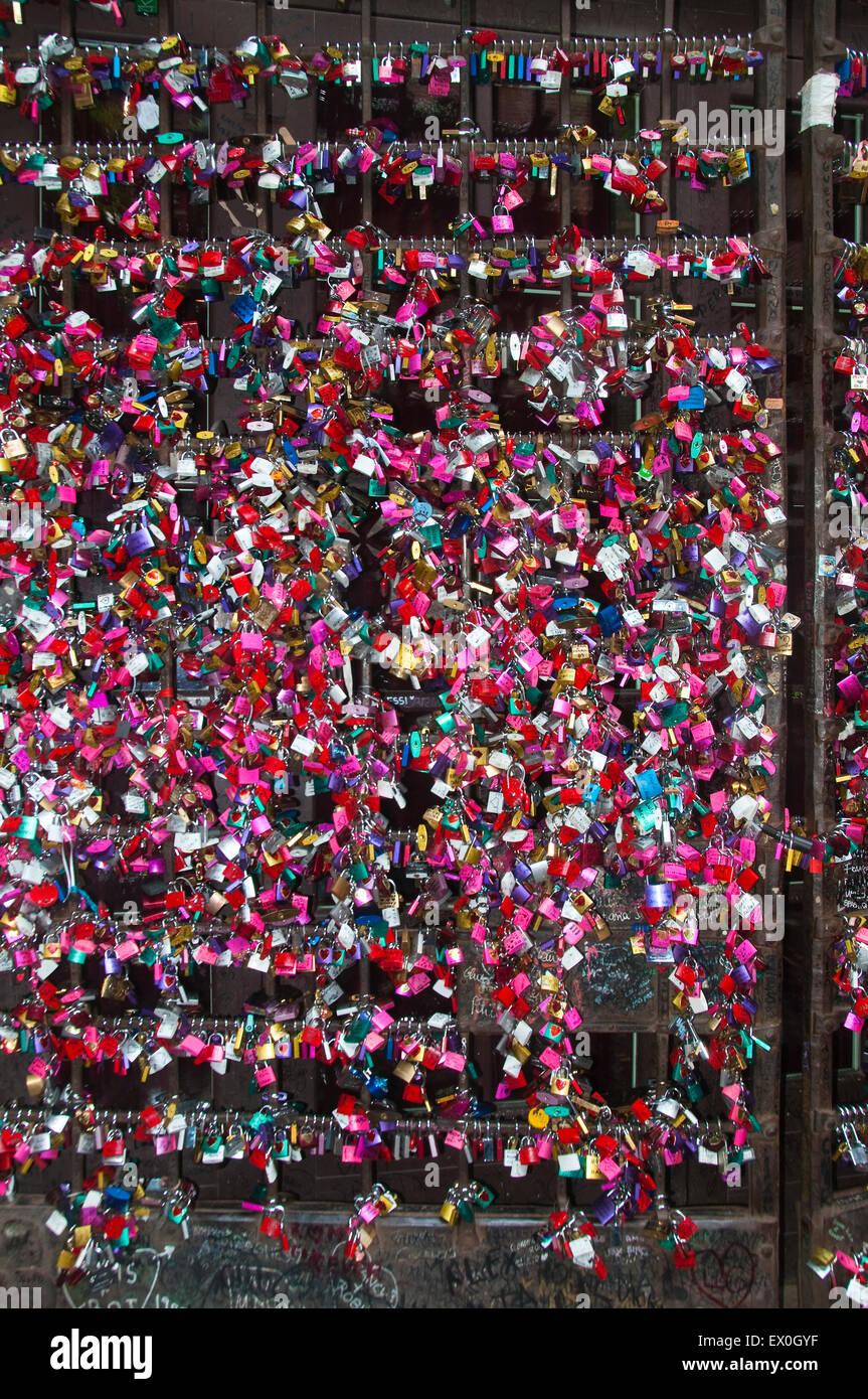De nombreux amateurs de couleur avec cadenas prénom le long d'un mur Photo Stock