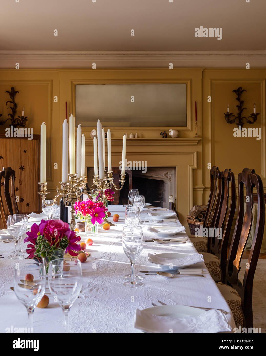 Candélabres sur table avec nappe en coton blanc et mobilier chaise de salle à manger Photo Stock