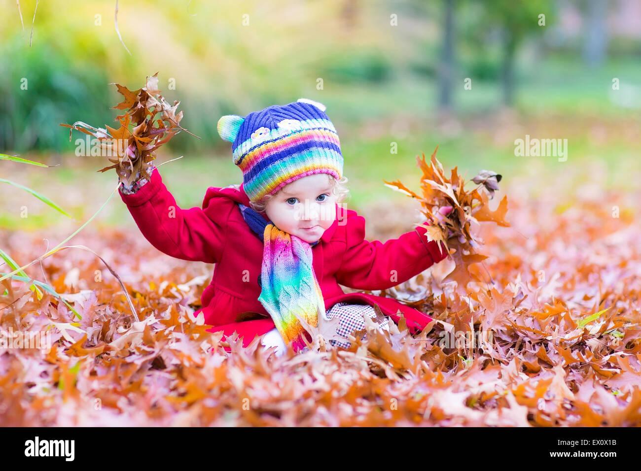 Adorable bébé fille avec un foulard et un chapeau coloré jouant avec  feuilles rouges dans un parc d automne 9aef72cd51e