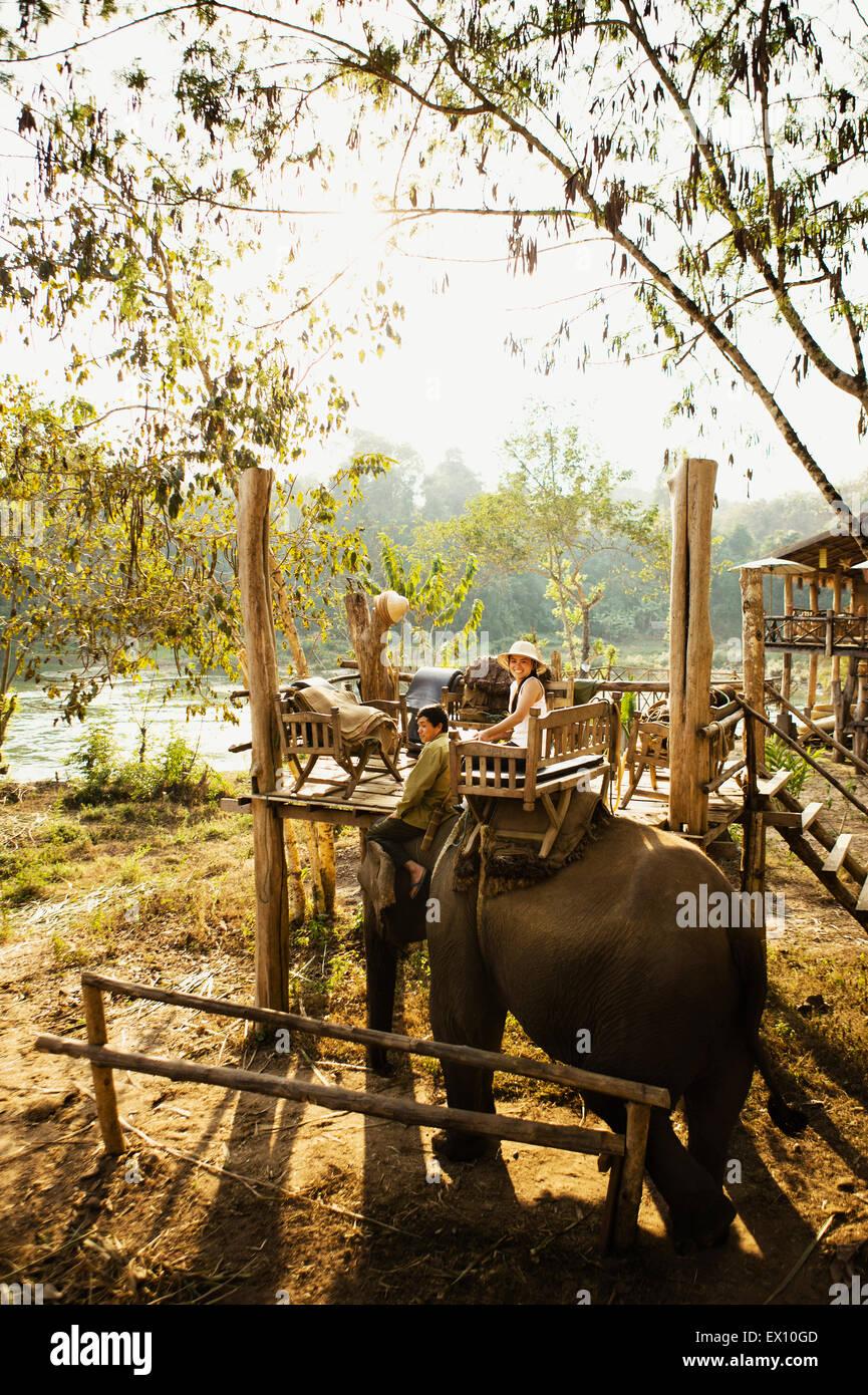 Une femme Lao et mahout ride un éléphant sur la Rivière Khan. Luang Prabang, Laos. Banque D'Images