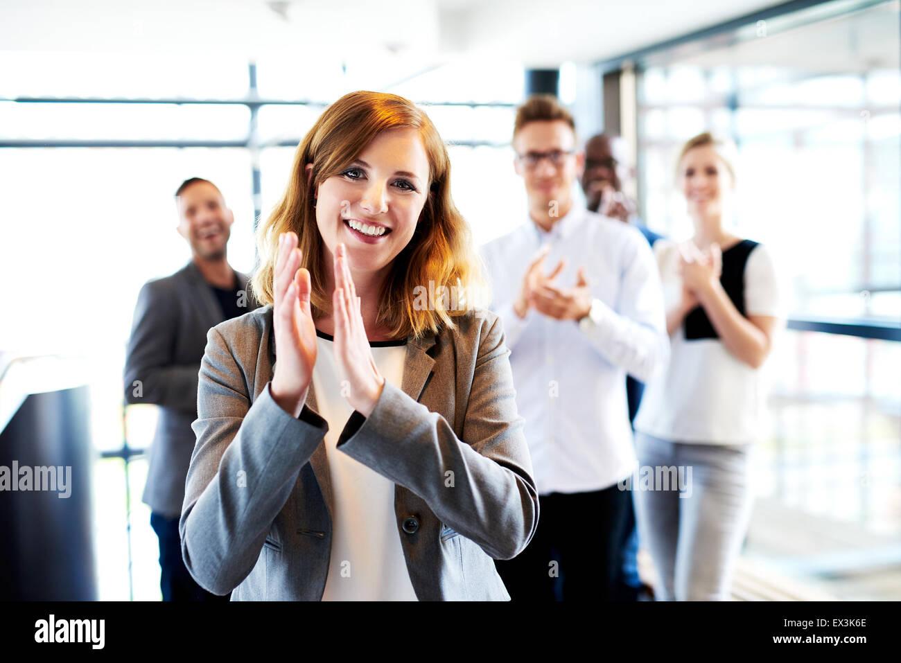 Jeune femme blanche directrice debout devant des collègues des mains et souriant Photo Stock