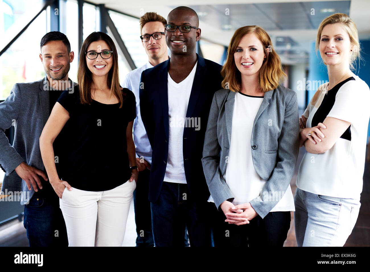Groupe de jeunes executives standing, smiling at camera et qui pose pour photo Photo Stock