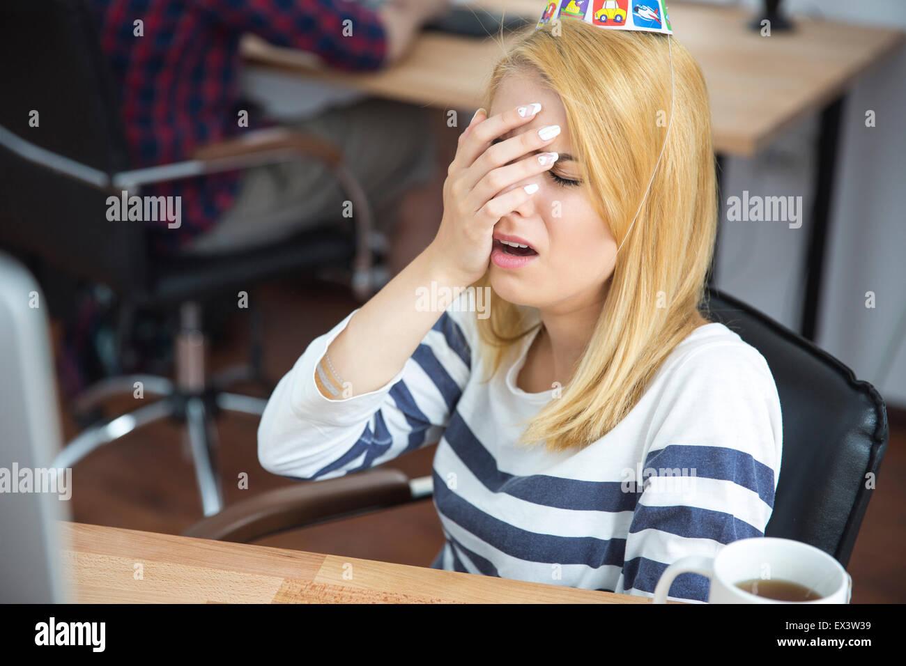 Frustré jeune femme assise à la table in office Photo Stock