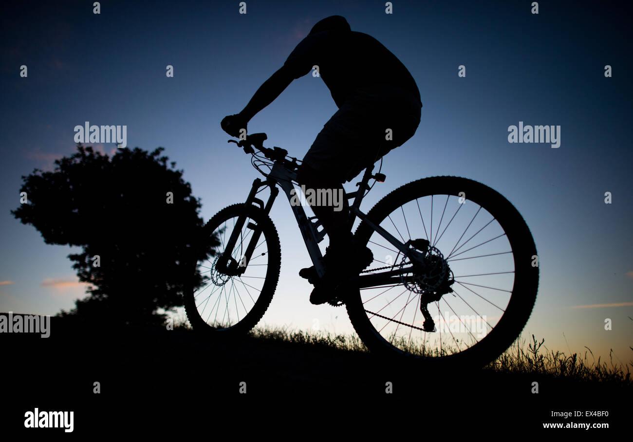 Hanovre, Allemagne. 01 juillet, 2015. Un homme conduit une bicyclette pendant le coucher du soleil sur la colline Photo Stock