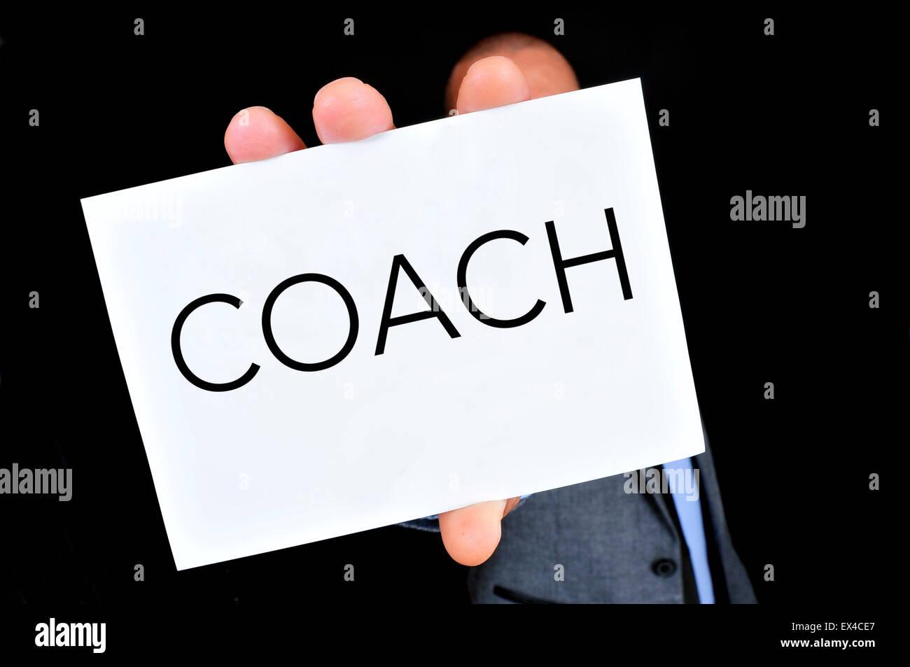 Un jeune homme de race blanche portant un costume gris et une chemise bleue montre une pancarte à l'entraîneur Photo Stock
