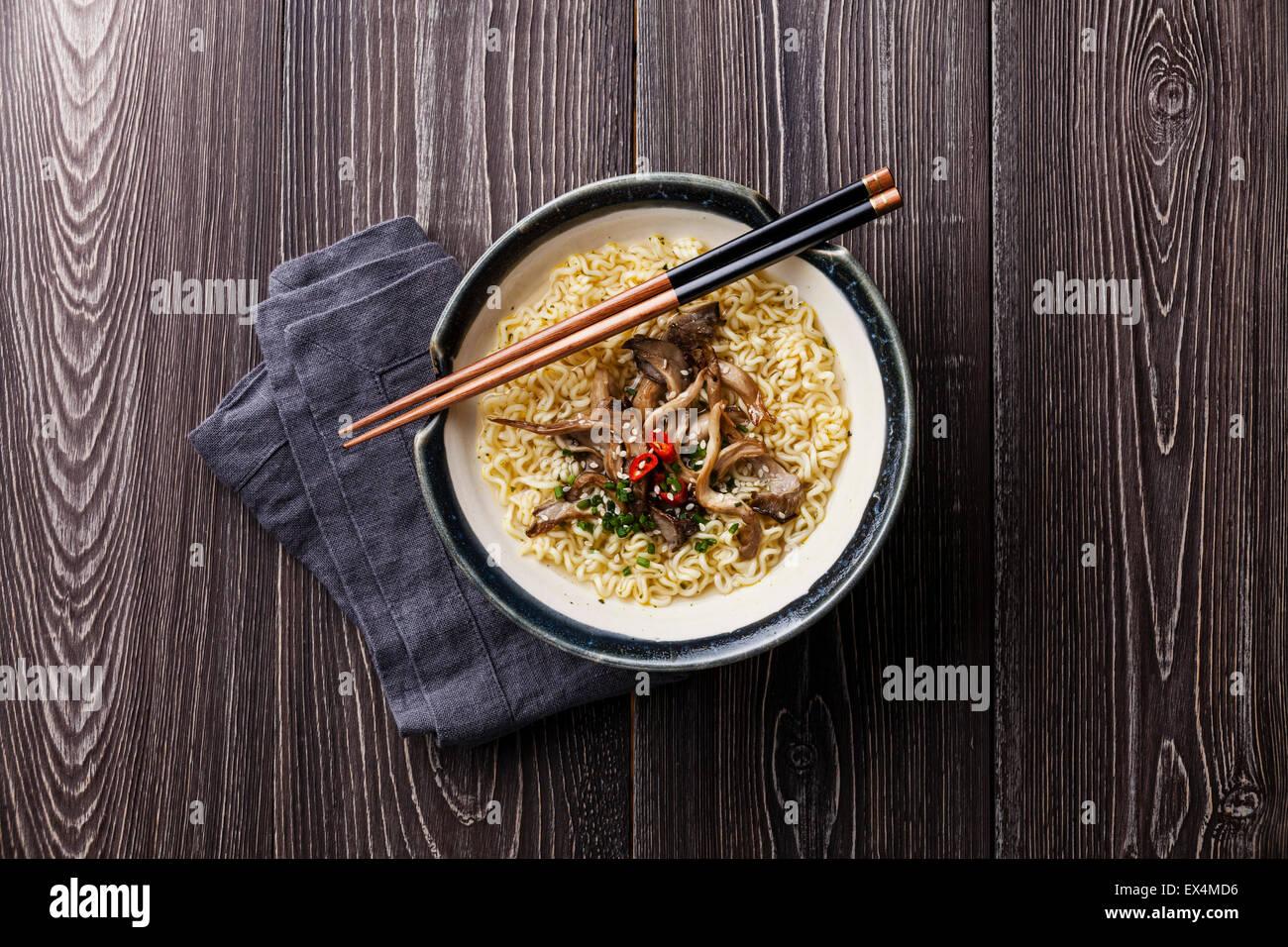 Nouilles asiatiques aux pleurotes en bol sur fond de bois gris Photo Stock