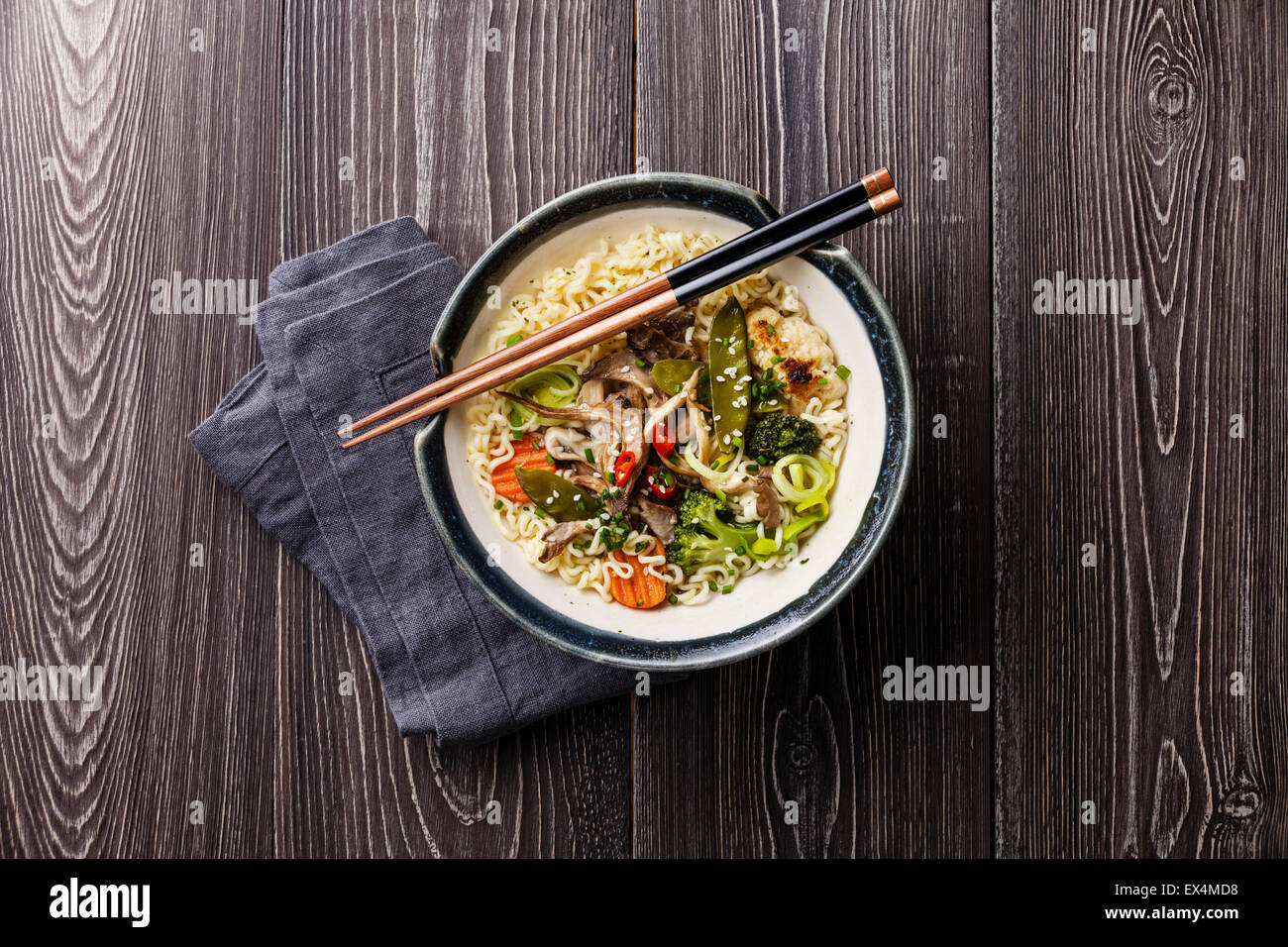 Nouilles asiatiques aux pleurotes et les légumes dans un bol sur fond de bois gris Photo Stock