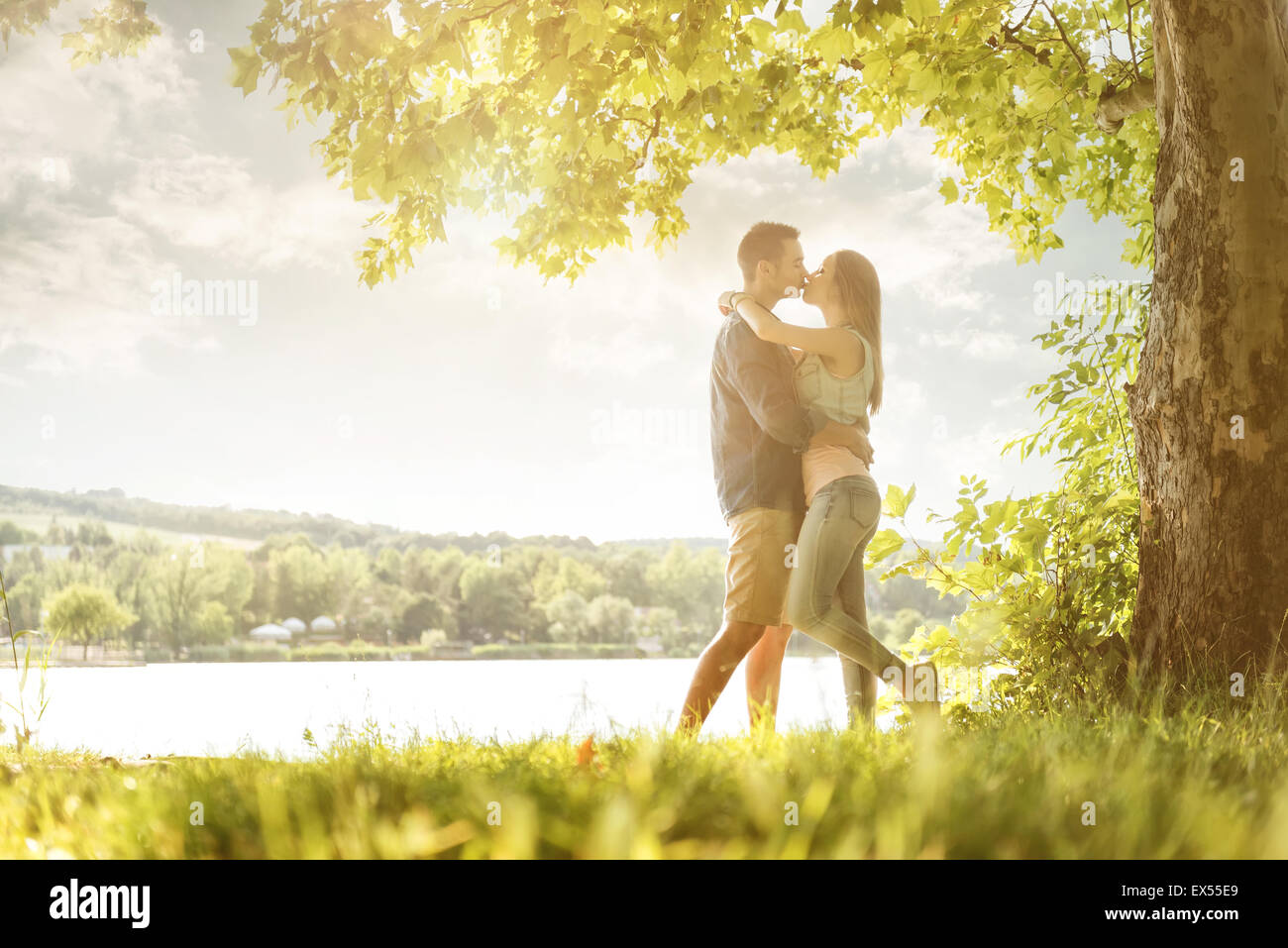 Couple in love sur le lac, sous les arbres, des baisers Photo Stock