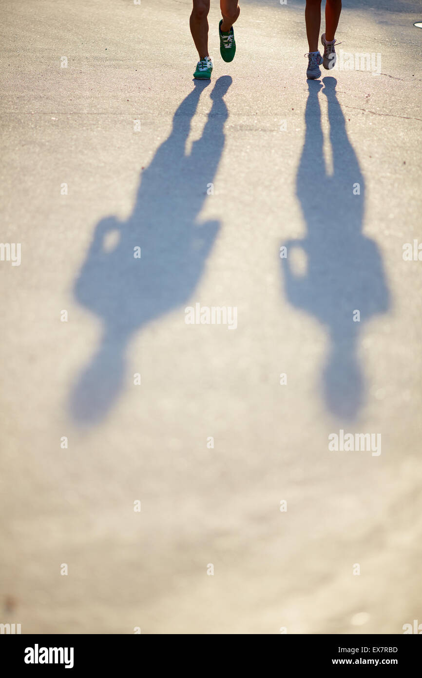 Deux paires de jambes en chaussures de sport et des ombres de couple sur la route d'asphalte Photo Stock