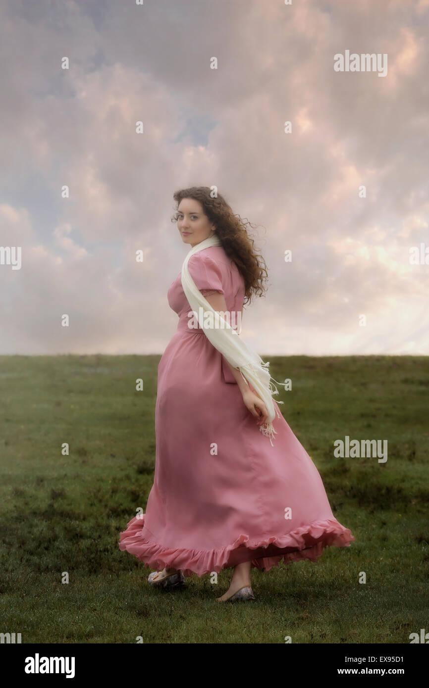 Une femme dans une robe rose est à monter une colline Photo Stock