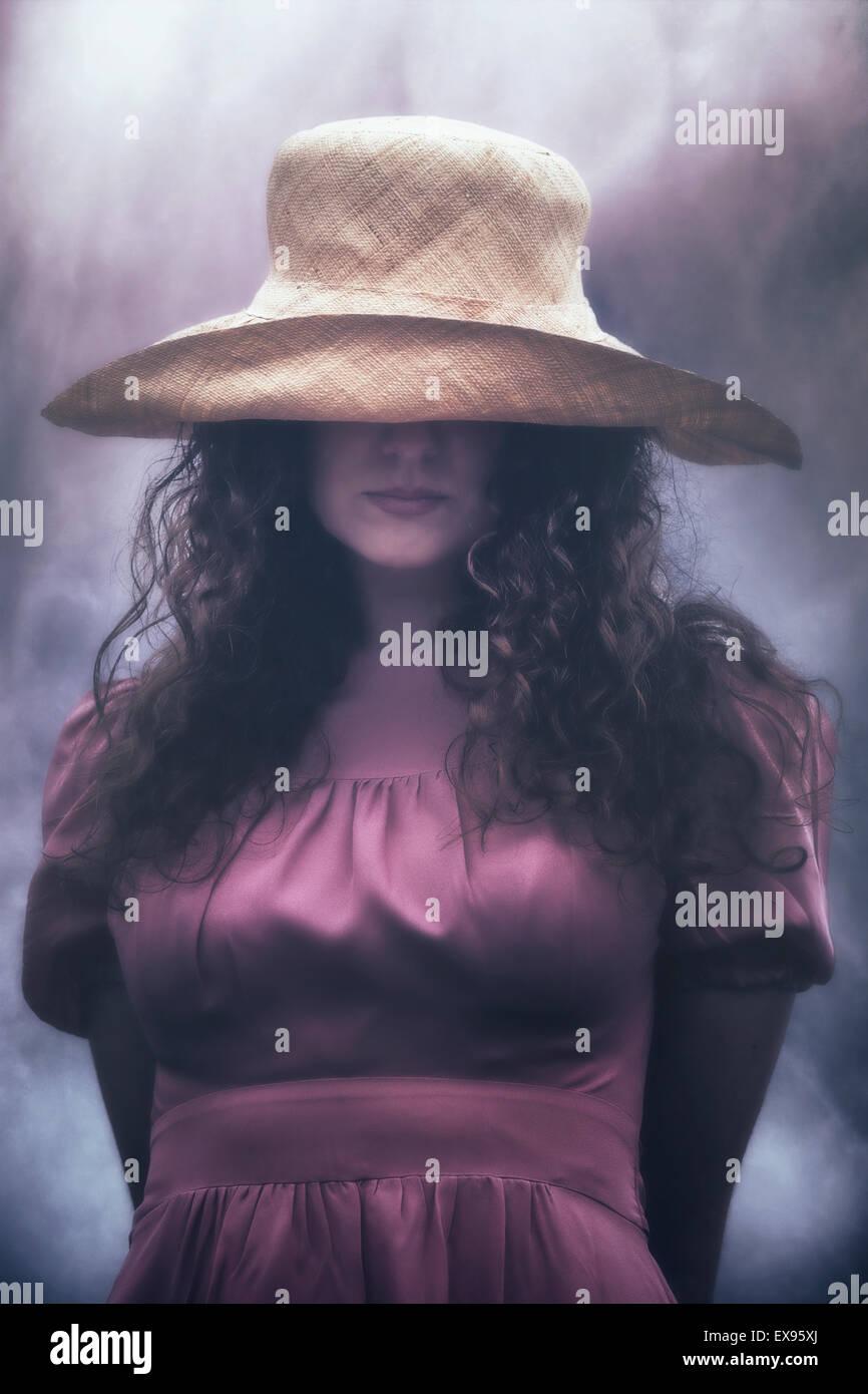 Une femme se cache derrière son chapeau Photo Stock