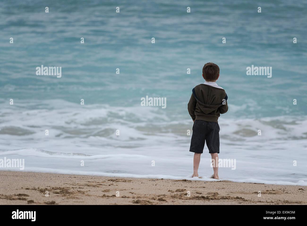 Un jeune garçon se tenant sur le rivage sur la plage de Fistral à Newquay, Cornwall Photo Stock