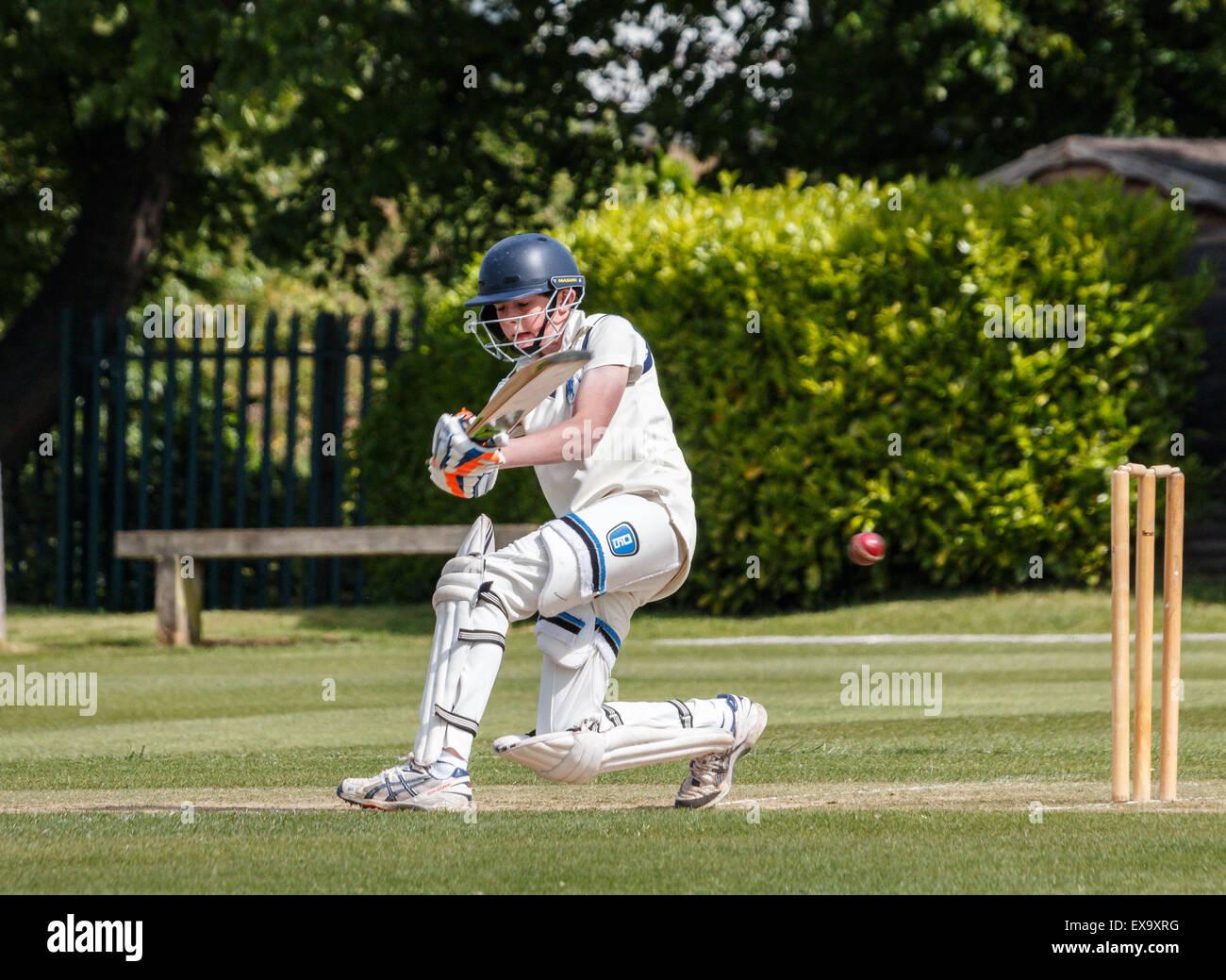 Un jeune batteur joue un coup de bâton alors que pendant un match de cricket de l'école. Il porte Photo Stock