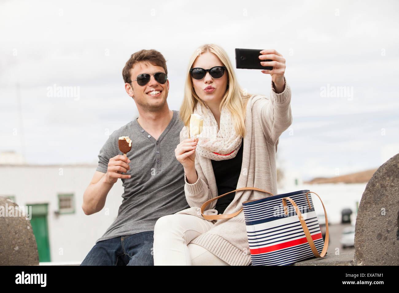 Jeune couple pousses selfies dans la ville Photo Stock