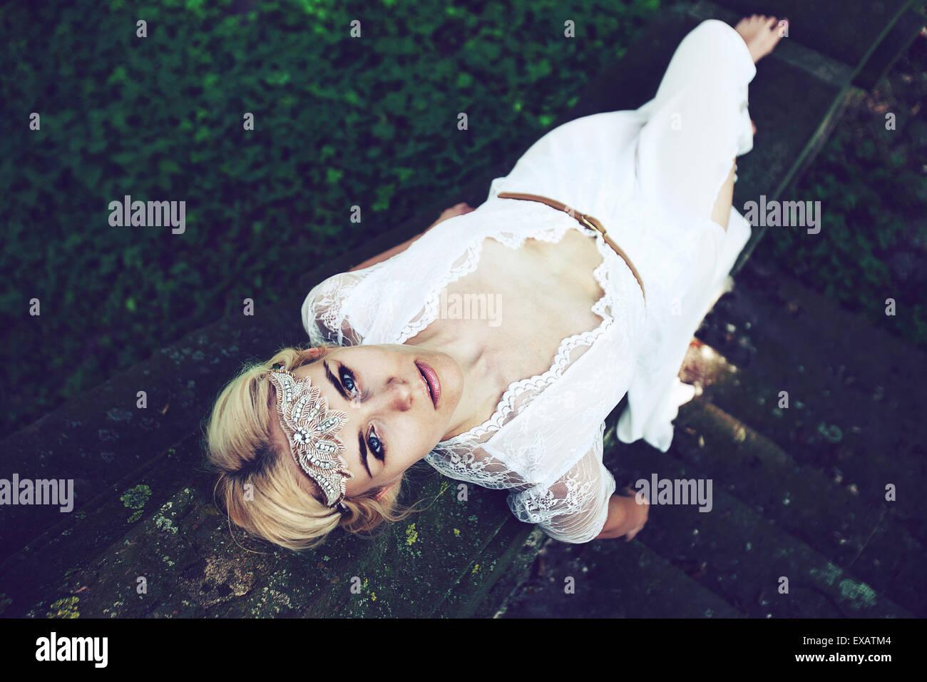 Jeune femme se trouve en haut des escaliers sur robe blanche dans le bois Photo Stock