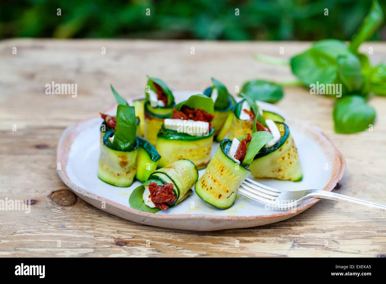 Rouleaux de courgettes au fromage de chèvre, tomates séchées et basilic Photo Stock