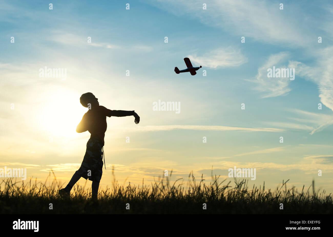 Garçon en train de lancer un modèle réduit d'avion au coucher du soleil. Silhouette Photo Stock
