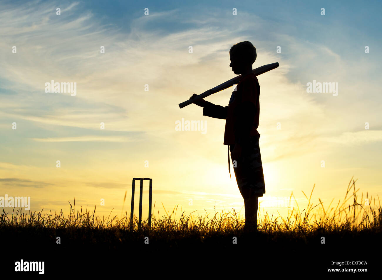 Silhouette de jeune garçon jouer au cricket contre un fond coucher de soleil Photo Stock