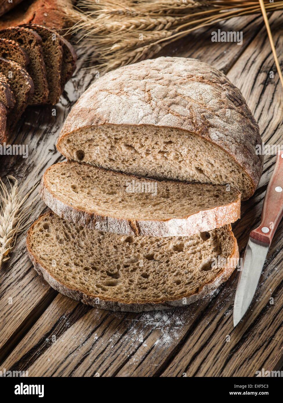 Tranches de pain noir sur la vieille planche de bois. Photo Stock