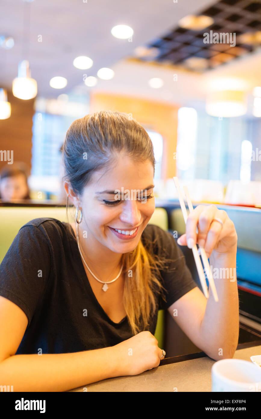 Jeune femme mange avec des baguettes en restaurant, Manille, Philippines Photo Stock