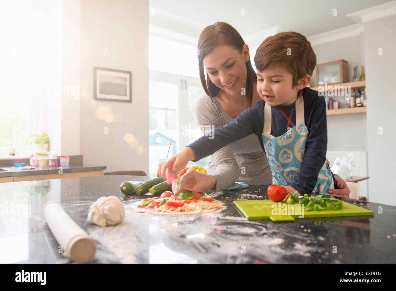 Mère et fils la préparation de pizza together in kitchen Photo Stock