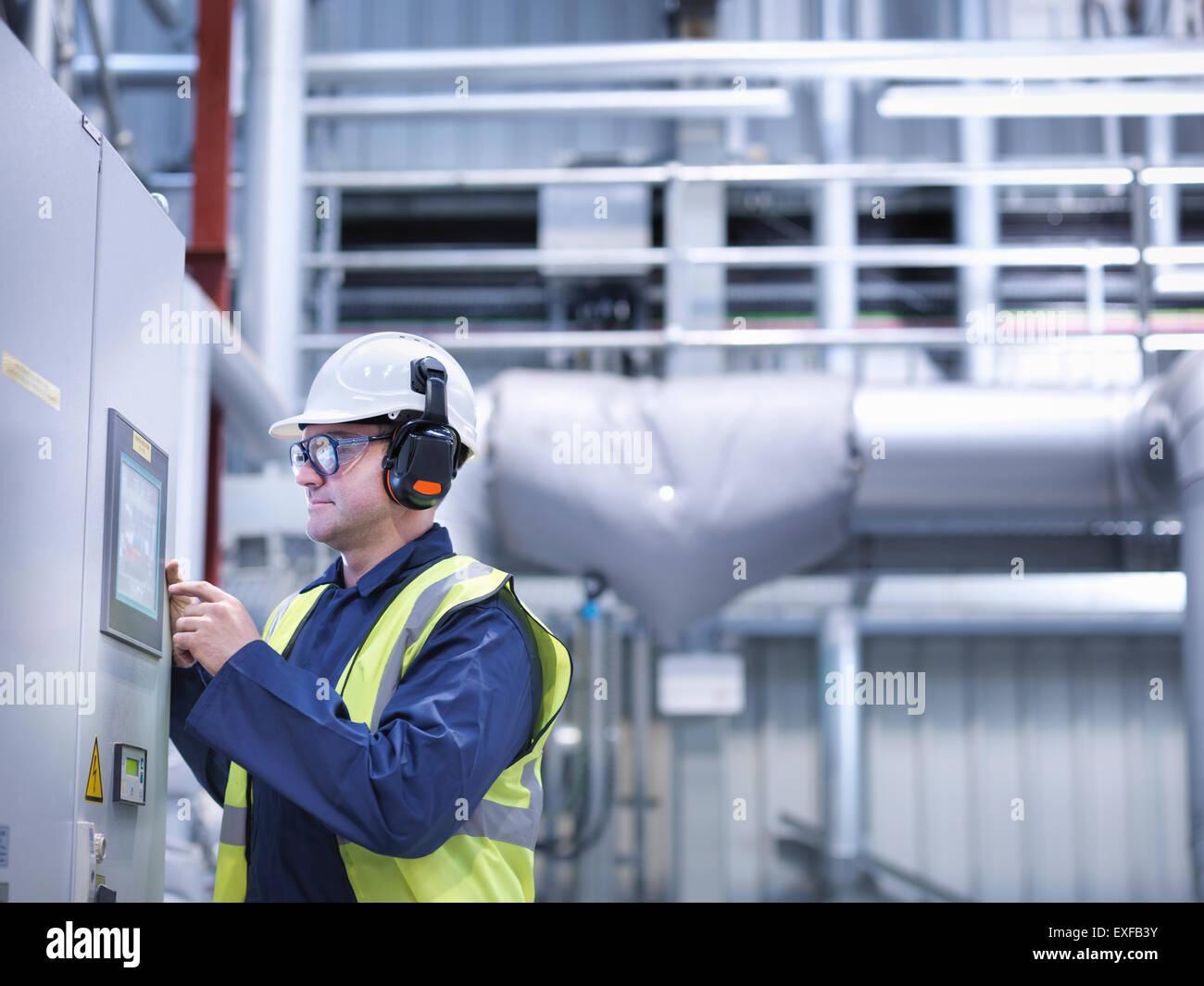 À l'aide des commandes de l'écran tactile du travailleur dans la station centrale au gaz Photo Stock