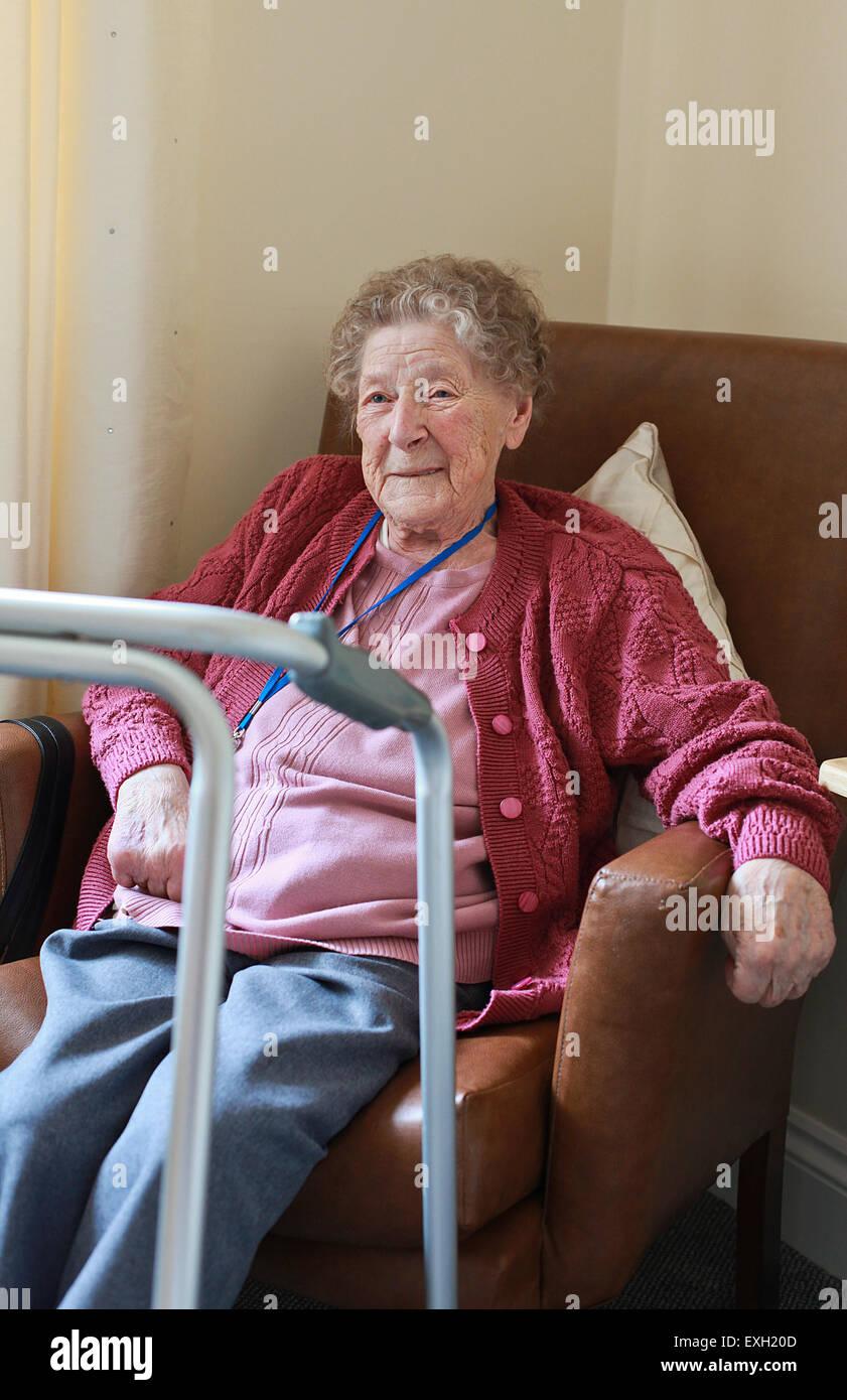 Portrait d'une femme assise dans un fauteuil dans une maison de soins de l'assistance à distance avec Photo Stock