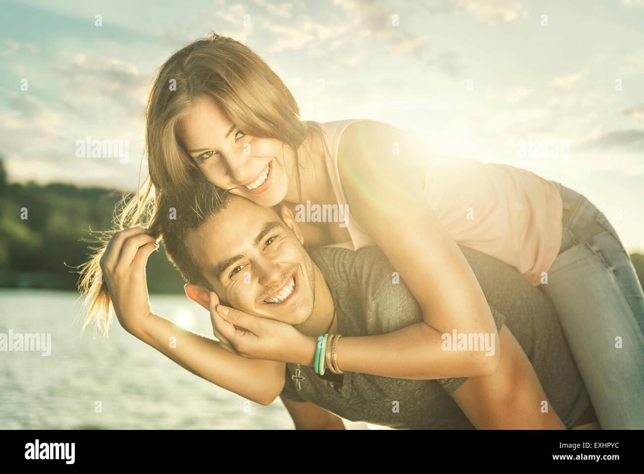 Couple in love embrassant au bord du lac, sun flare Photo Stock