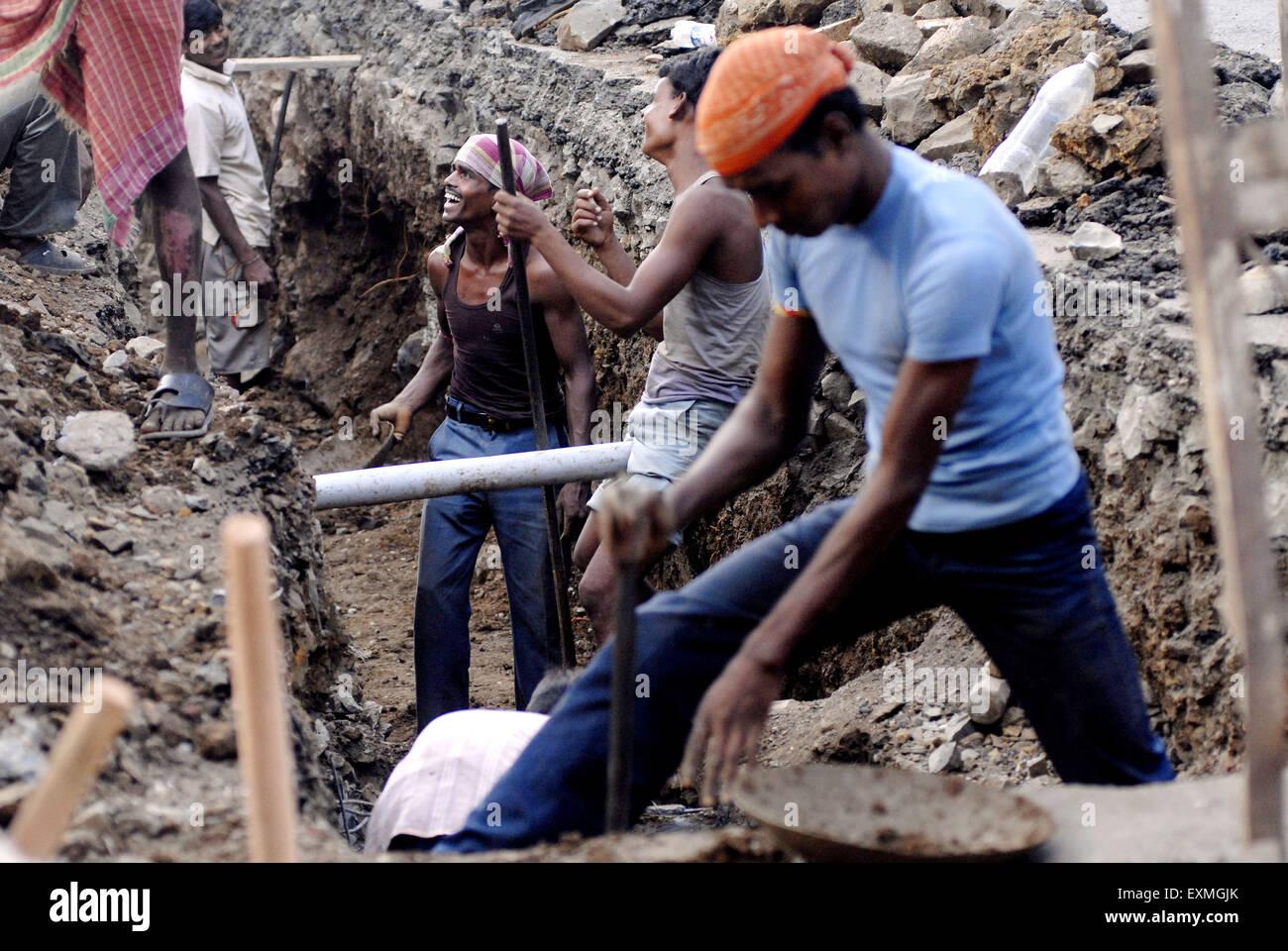 La construction de routes les travailleurs partagent une blague comme ils creusent la route d'établir un Photo Stock