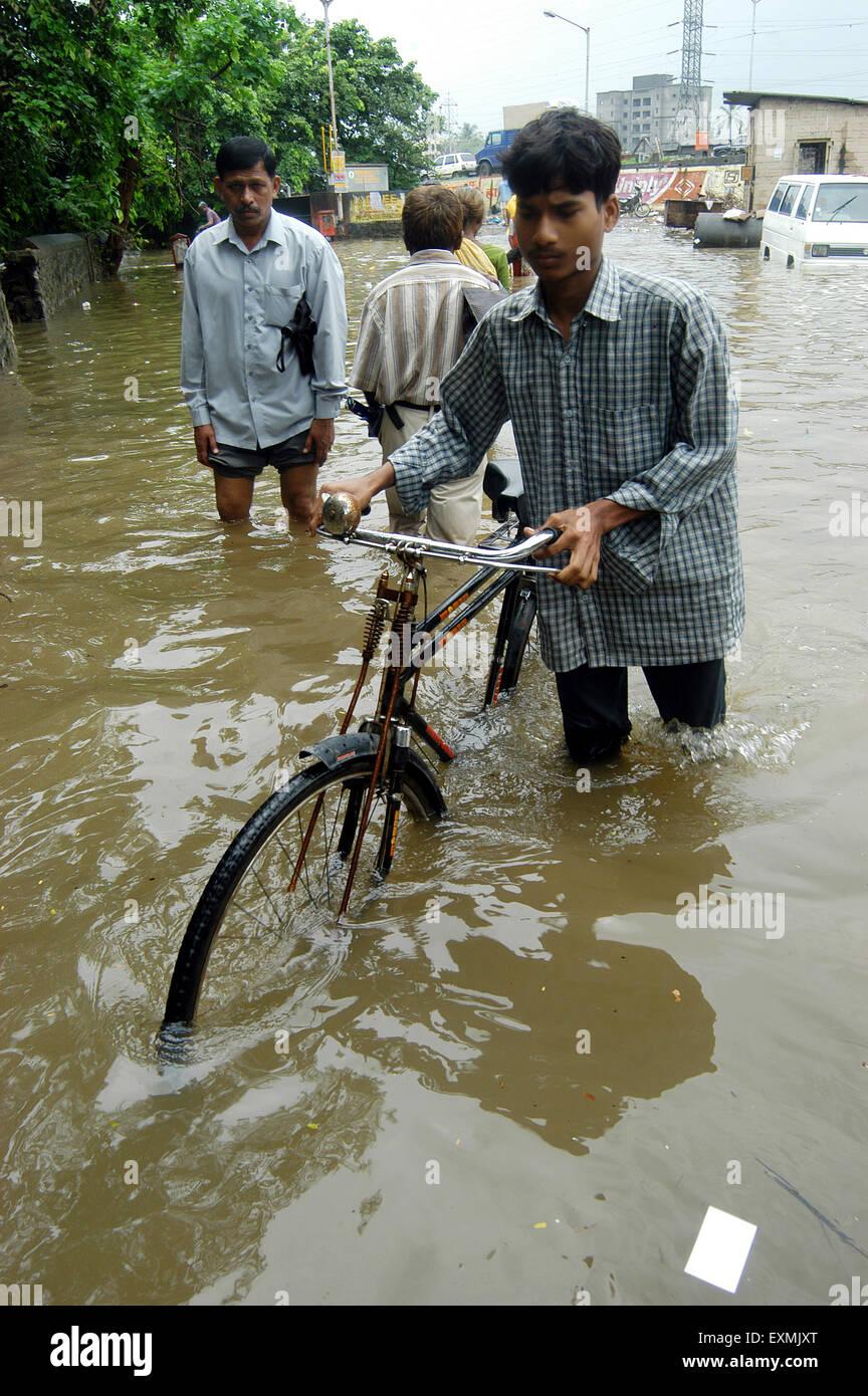 Faites glisser le cycliste dans le cycle de l'eau inondation causée en raison de fortes pluies dans la Photo Stock