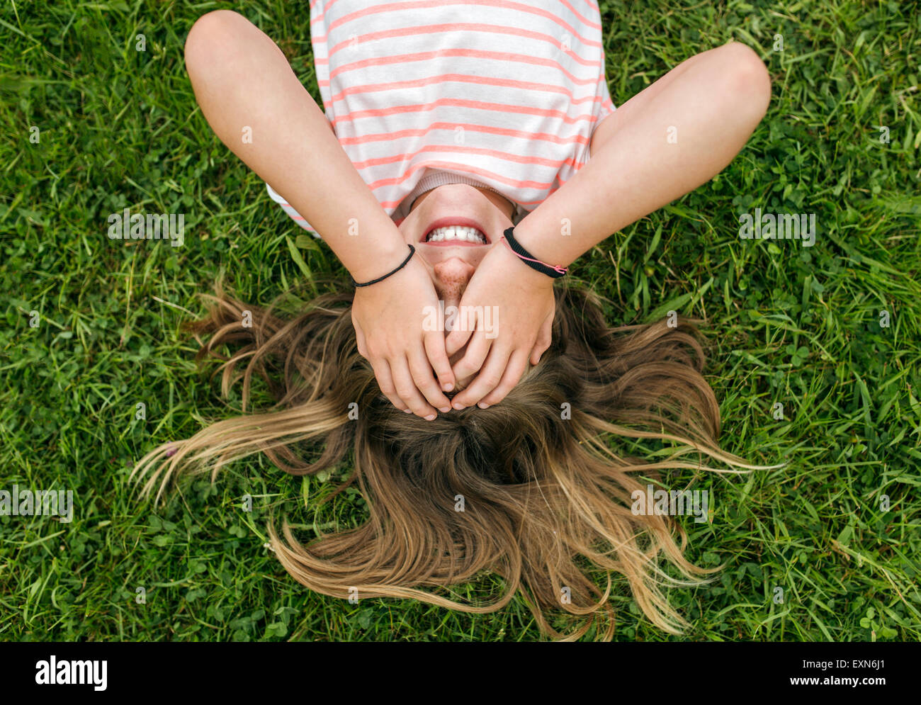 Girl lying on a meadow couvrant les yeux avec ses mains Photo Stock