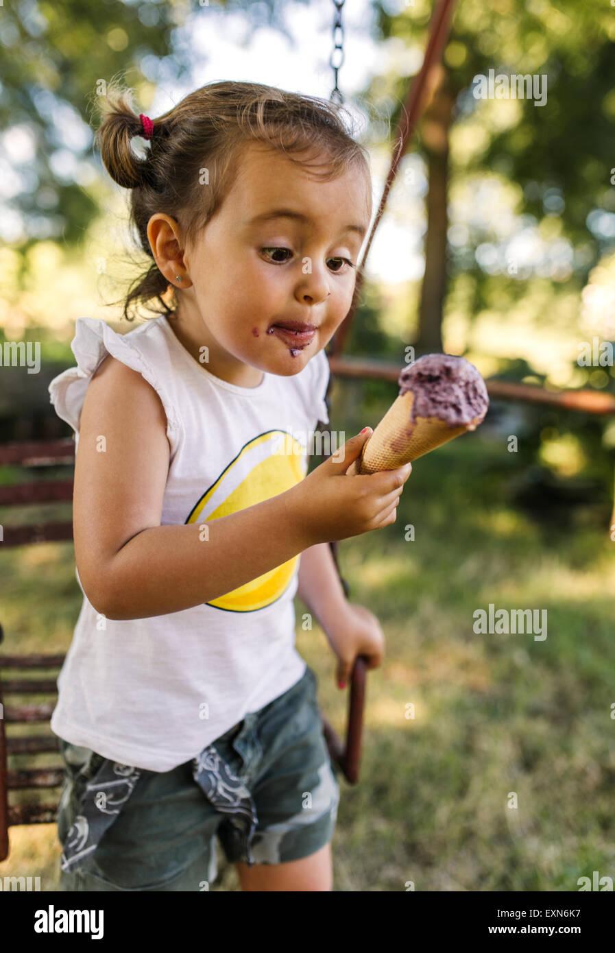 Petite fille en essayant de manger la crème glacée Photo Stock