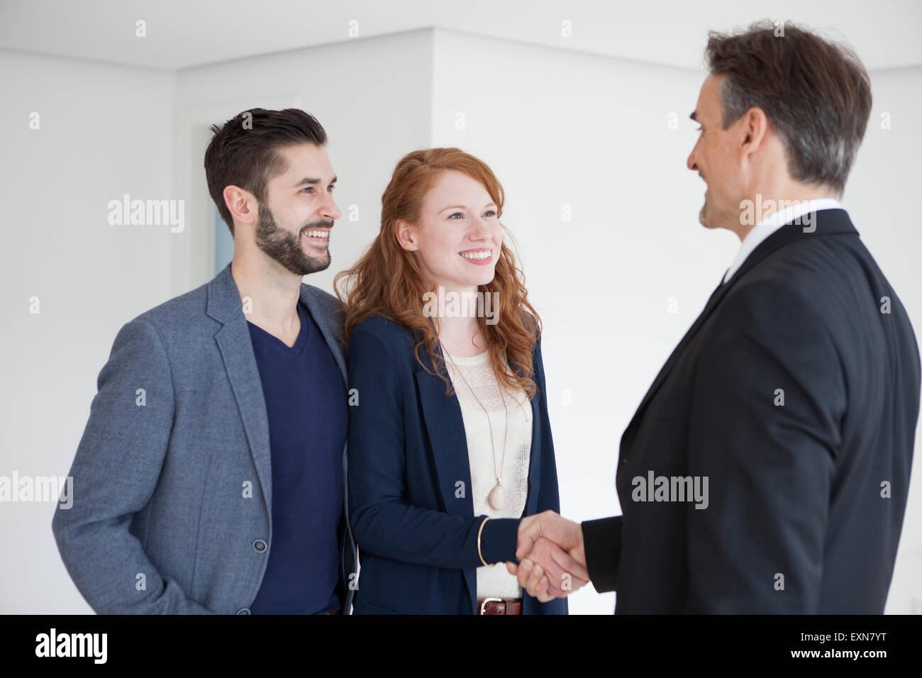 Jeune couple télévision affichage avec agent immobilier Photo Stock