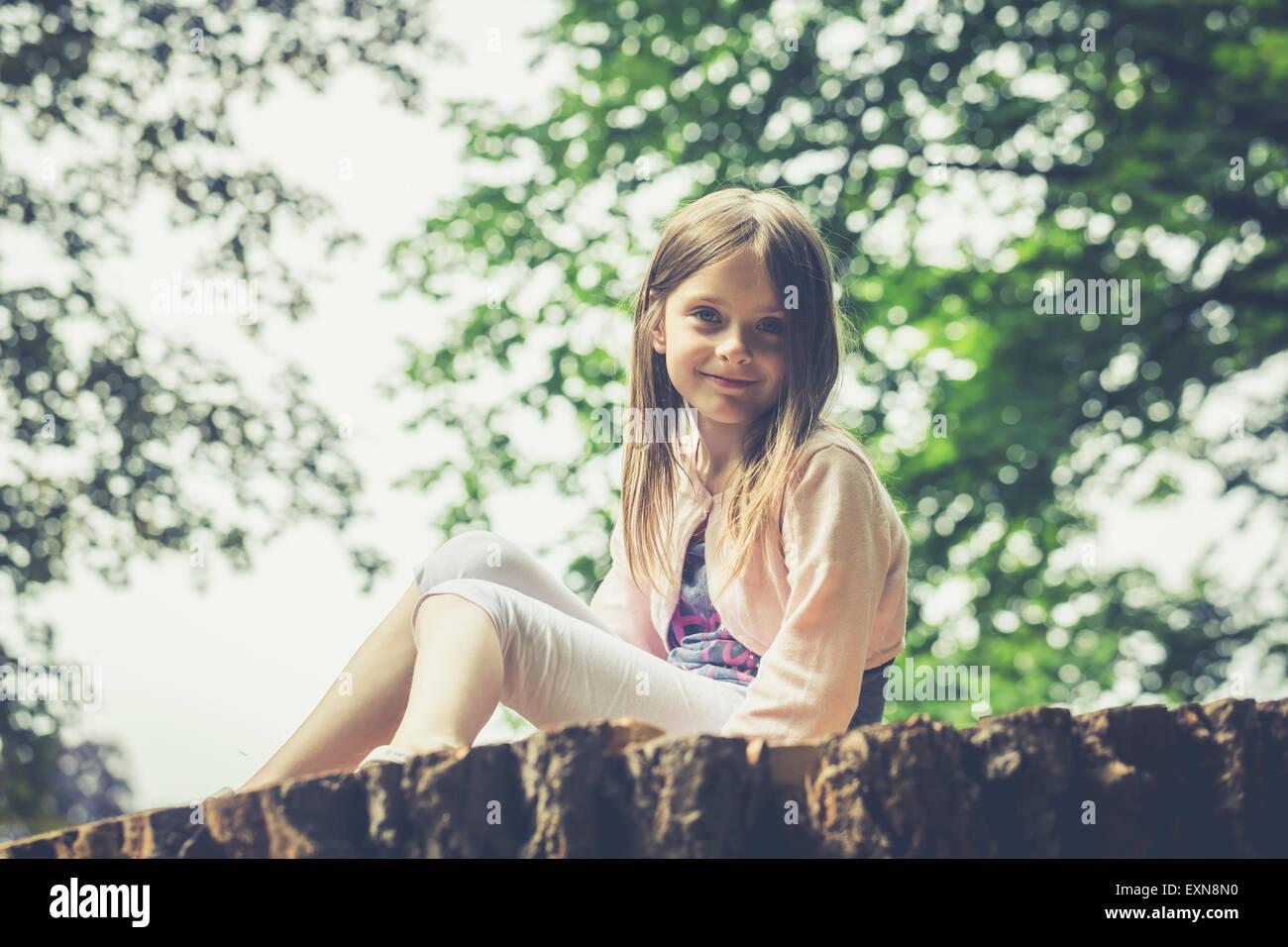 Portrait de petite fille assise sur le grand tronc de l'arbre Photo Stock