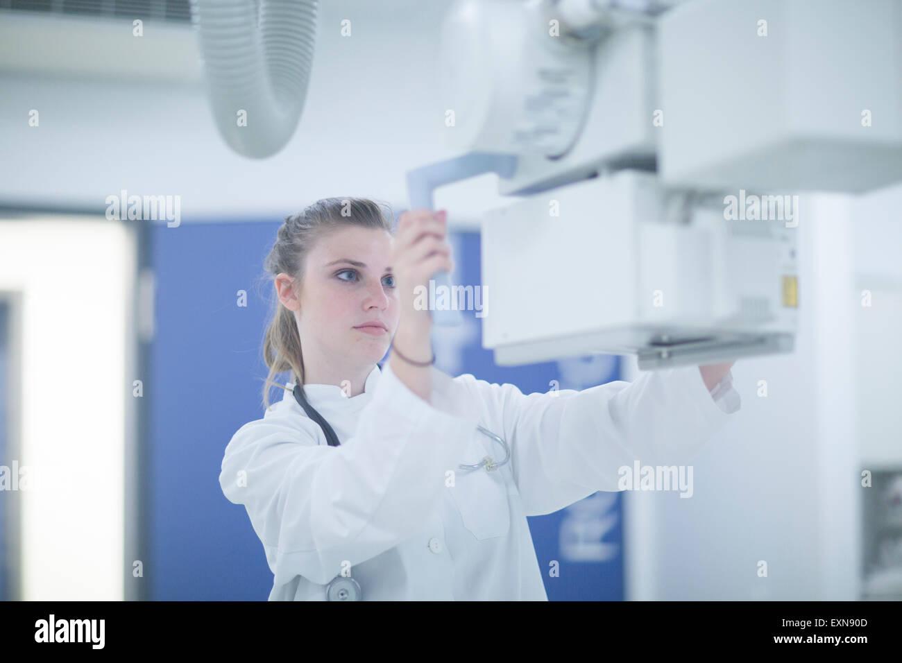 Jeune médecin à l'hôpital d'ajustement à l'unité à rayons x Photo Stock