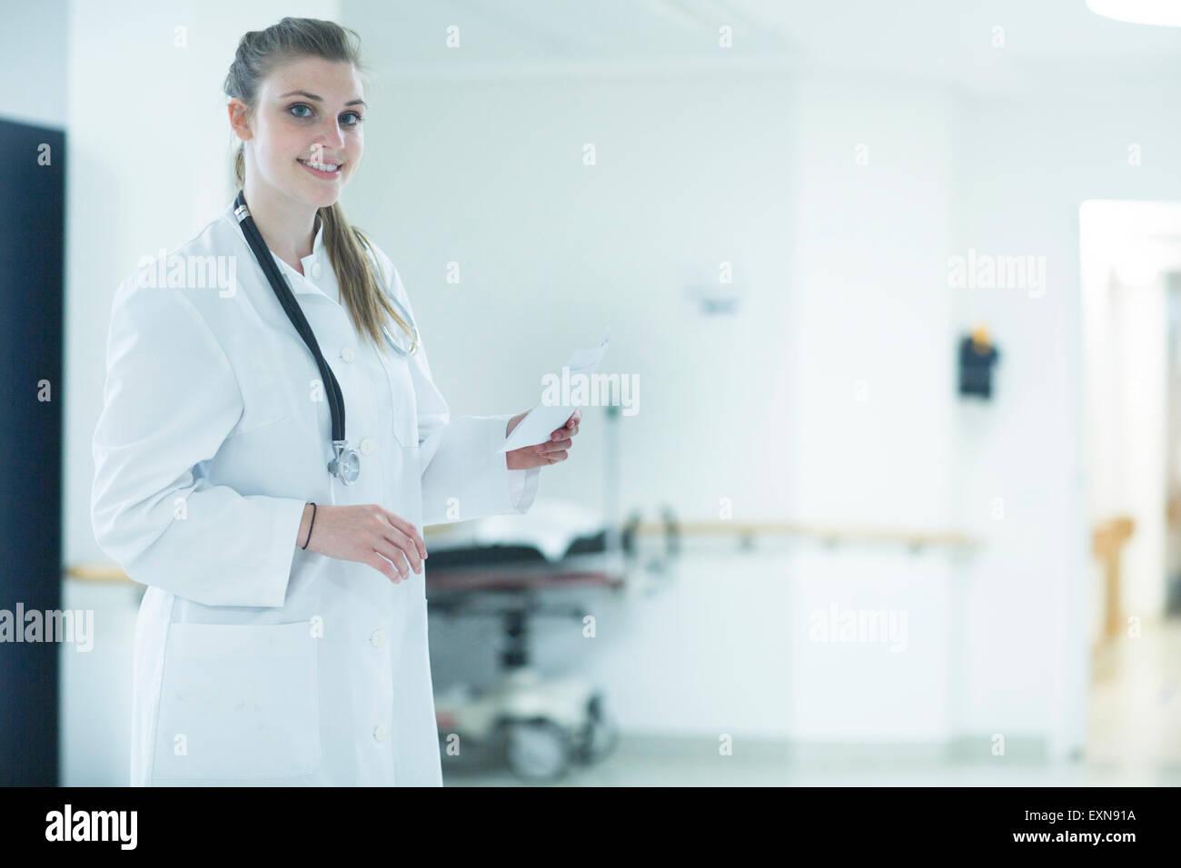 Portrait of smiling young docteur à l'étage de l'hôpital Photo Stock