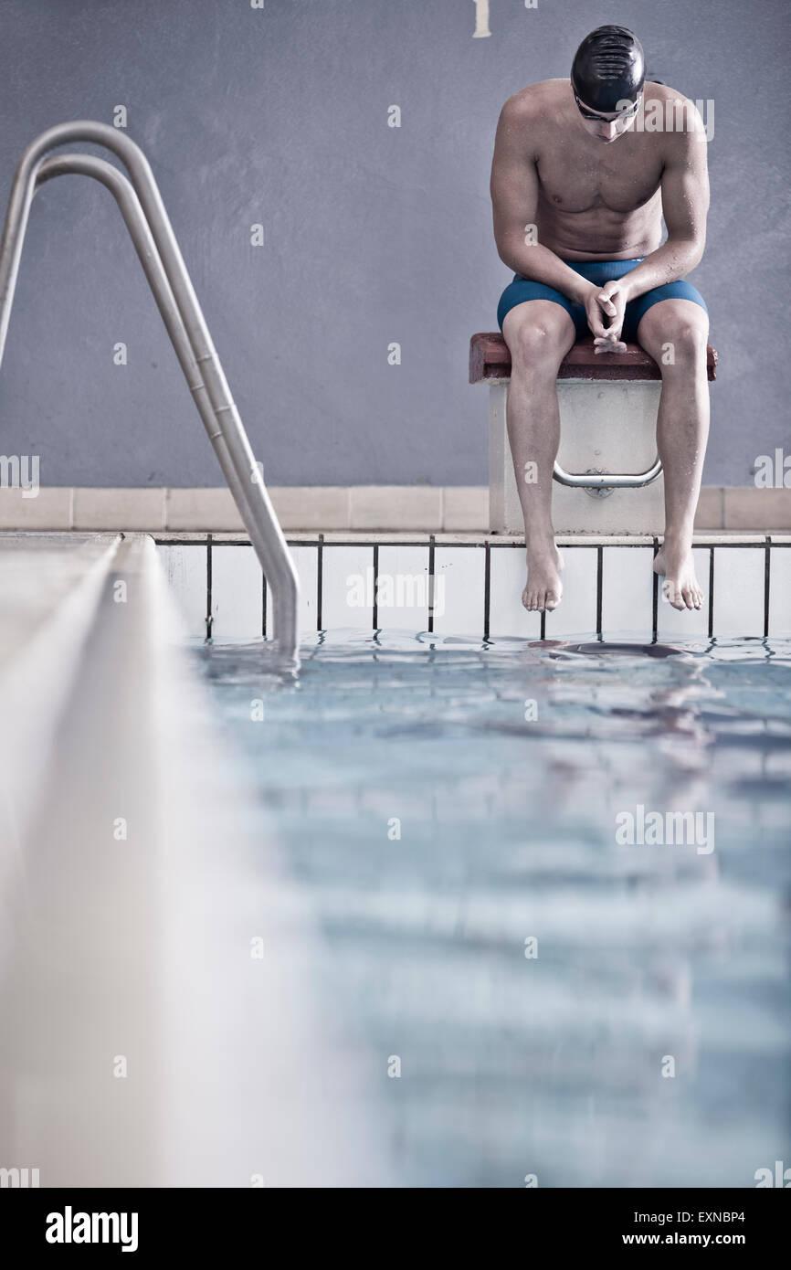 Nageur dans une piscine intérieure assis sur bloc de départ Photo Stock
