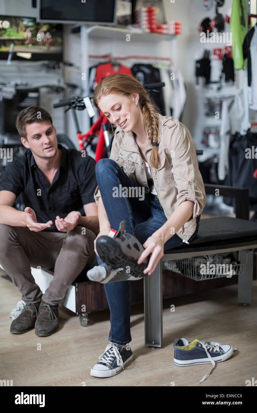 76403b089bbb06 Jeune femme l'achat des chaussures de vélo, vendeur conseiller ...